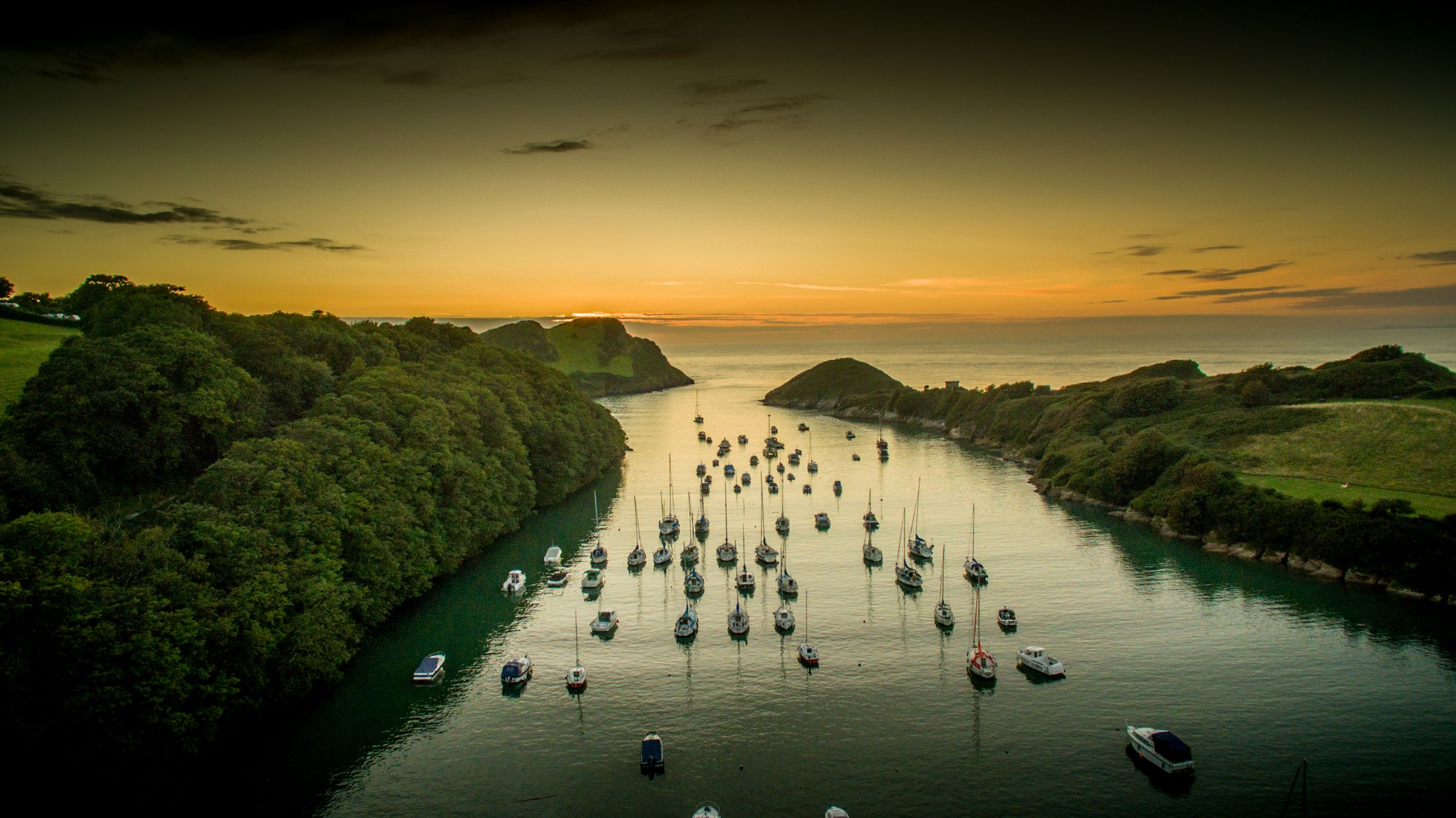 Watermouth Cove at sunset over water with small boats.