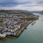 Drone image featuring Dartmouth Harbour. Fishing boats in the water and the Naval College on the hill. Shops and Houses on the hill.