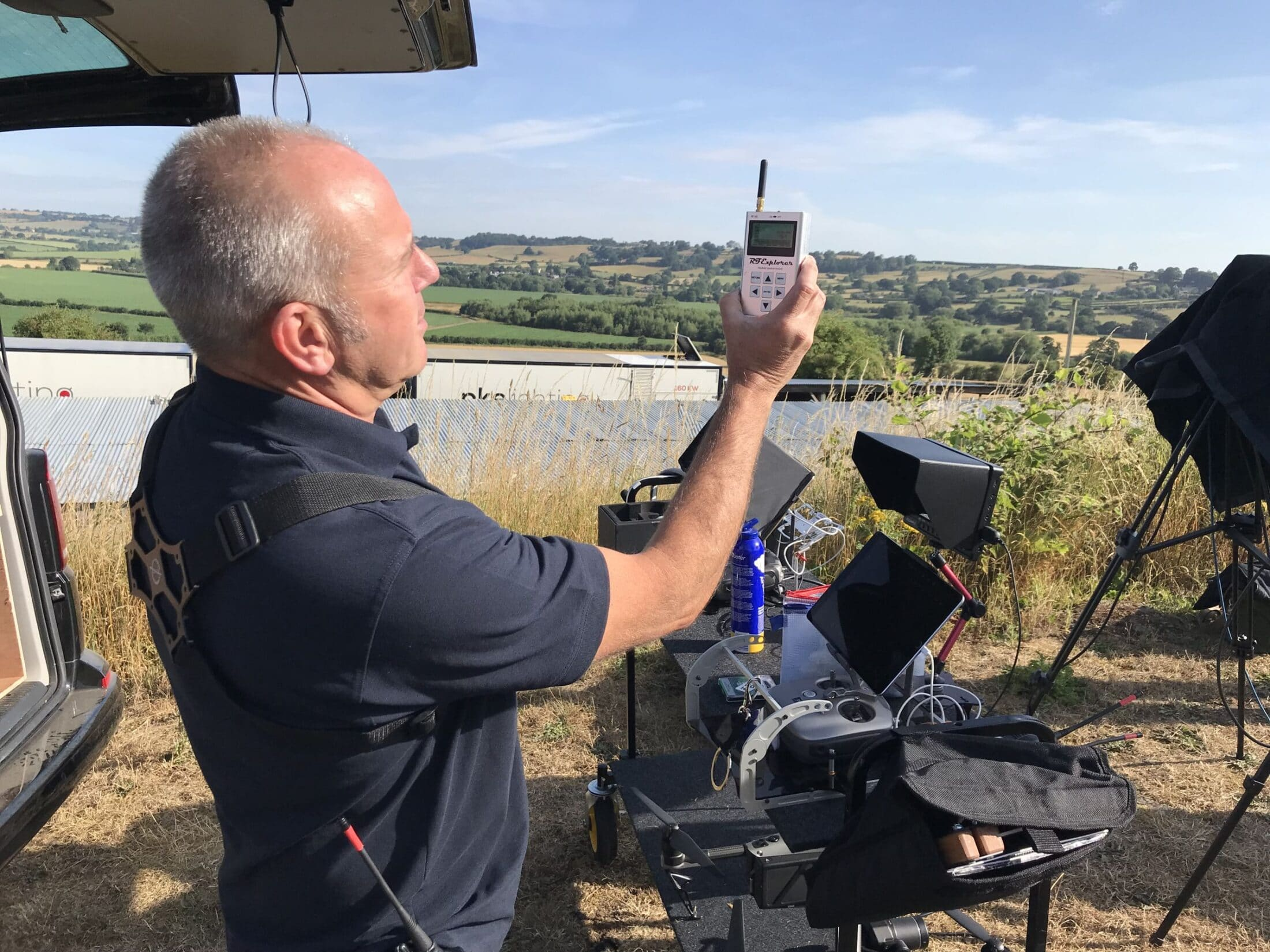 Darren Miller checking Radio Waves stood with the drone remote control, trees , grass and fields