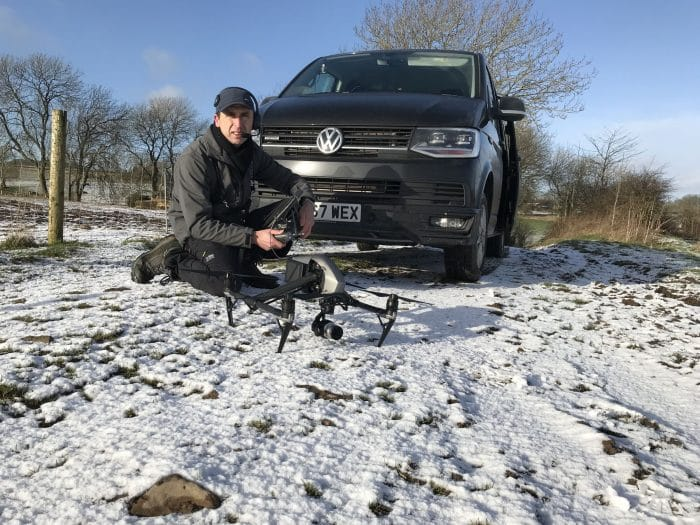 Pilot with drone and VW Transporter and snow