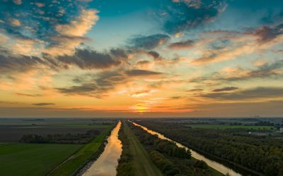 Drone over two rivers at sunset featuring bright lit up sky.