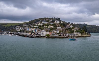 Dartmouth Harbour with boats and houses on a hill. The sea is in the foreground with dark skies.