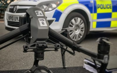 DJI Inspire 2 drone on a work table with a fake police car in the background.