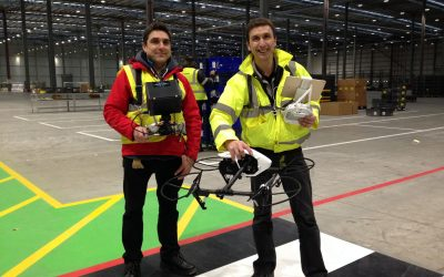 filming Indoors with a drone. Cameraman Ian Fearnley and Drone Pilot Phil Fearnley. Dressed in His Visibility safety clothing. Filming in a large warehouse